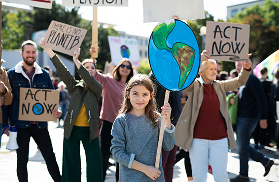 People and children with placards and posters on global strike for climate