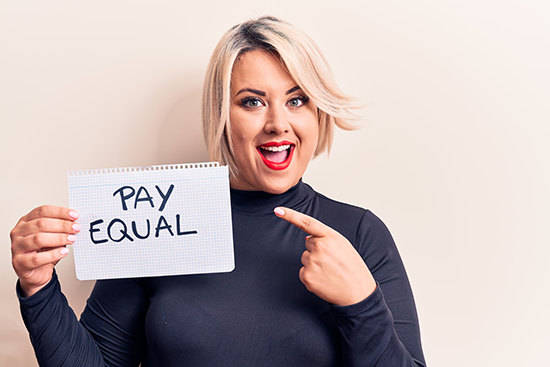 Beautiful Plus Size Woman Asking For Equality Economy Holding Paper that says Pay Equal and Fair Wages